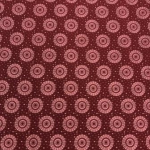 maroon coloured shweshwe fabric with sun circle designs